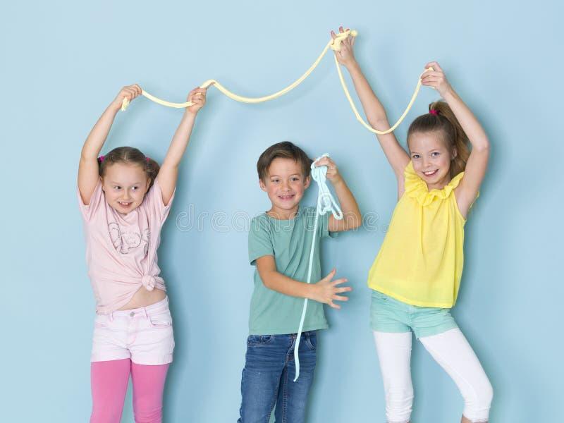 Dois bonitos e meninas engraçadas e um menino fresco que jogam com muito limo na frente do fundo azul e que têm muito divertiment fotos de stock royalty free
