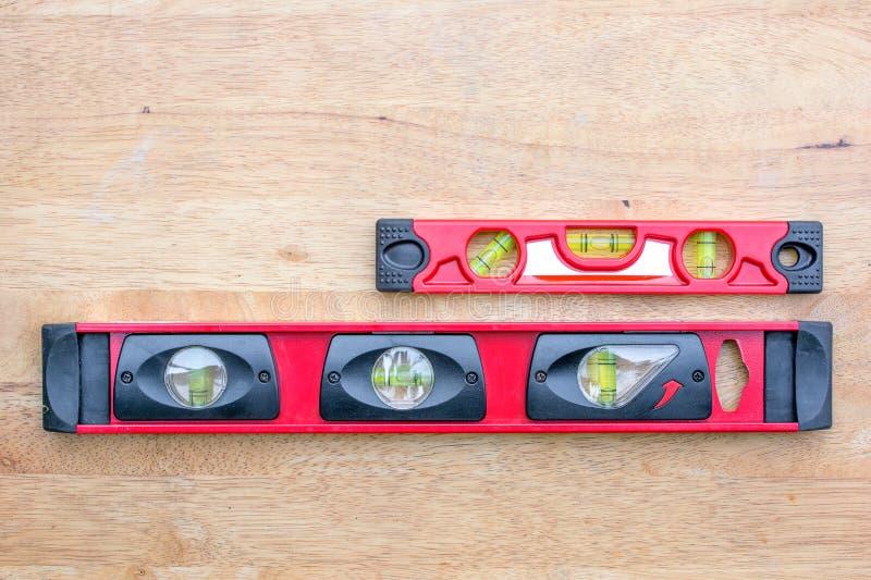 Dois bonitos nível vermelho do construtor no fundo de madeira da tabela foto de stock