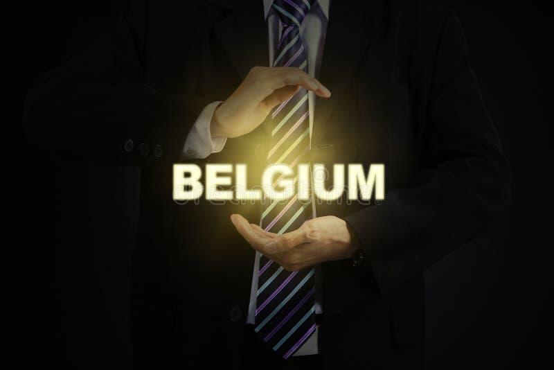 Dois braços que guardam uma palavra brilhante de Bélgica foto de stock royalty free