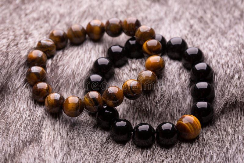 Dois braceletes de pedras redondas na pele cinzenta imagem de stock royalty free