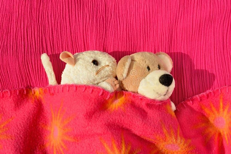 Dois brinquedos macios que afagam na cama imagens de stock royalty free