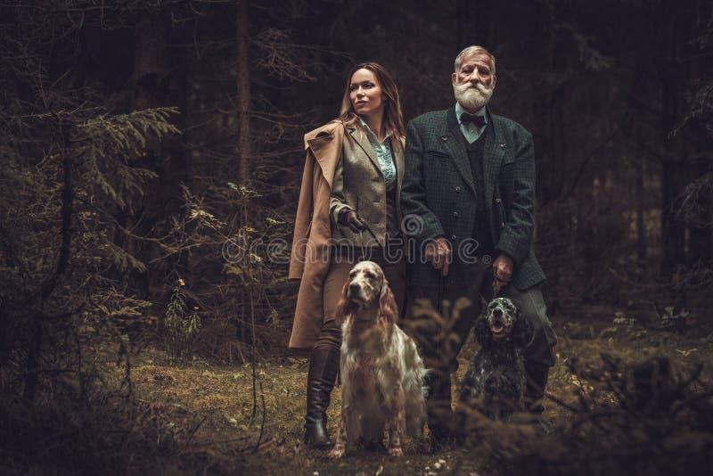 Dois caçadores com cães e espingardas em uma roupa tradicional do tiro, levantando em um fundo escuro da floresta foto de stock royalty free