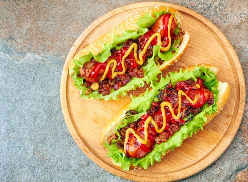 Dois cachorros quentes caseiros com coberturas da alface, do bacon e da cebola fotografia de stock royalty free