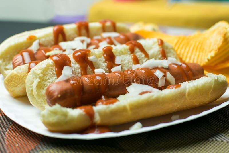 Dois cachorros quentes do estilo de New York com ketchup, mostarda, cebolas, e um lado de microplaquetas de batata, serviram em u foto de stock