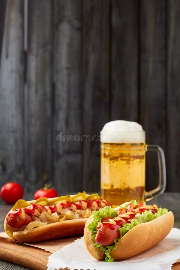 Dois cachorros quentes e canecas de cerveja fotos de stock