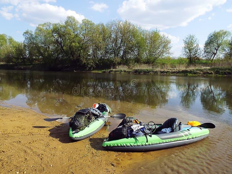 Dois caiaque infláveis verdes com equipamento no rio no verão fotografia de stock