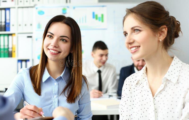 Dois caixeiros fêmeas caucasianos bonitos de sorriso que discutem no escritório alguns problemas de negócio foto de stock