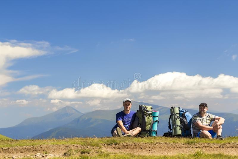 Dois caminhantes com as trouxas que sentam-se em um monte com as montanhas em vi fotografia de stock