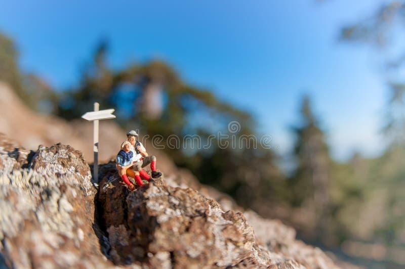 Dois caminhantes com a trouxa que relaxa sobre uma montanha imagens de stock