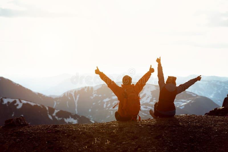 Dois caminhantes na parte superior da montanha com braços aumentados fotos de stock