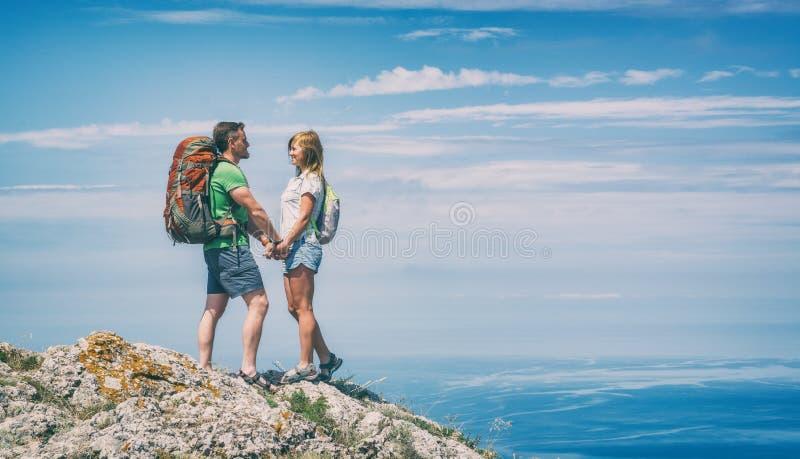 Dois caminhantes novos em uma parte superior da montanha fotografia de stock royalty free