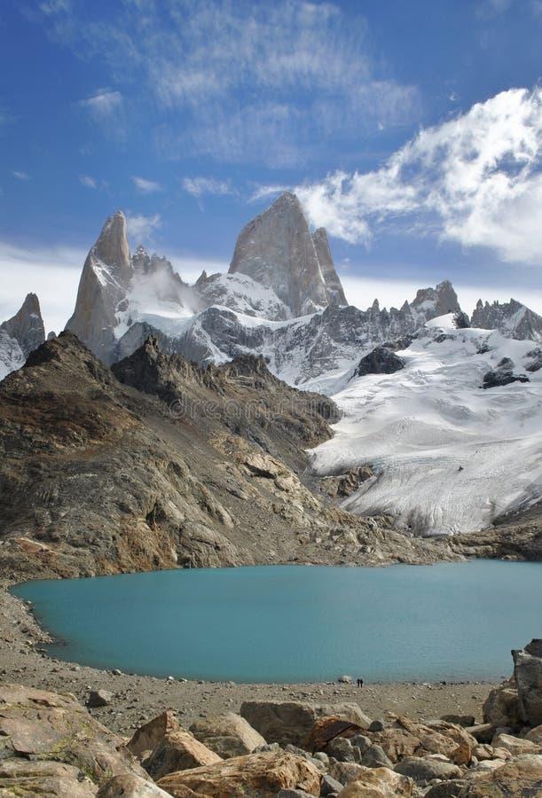 Dois caminhantes que sentem a posição pequena na frente da montanha maciça de Fitz Roy com ela são esmeralda bonita um lago color imagem de stock royalty free
