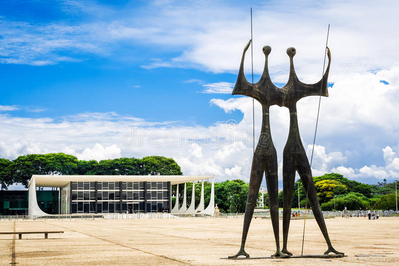 Dois Candangos Monument in Brasilia, Capital of Brazil. View of Three Powers Square including Os Guerreiros (or Dois Candangos) monument and Federal Supreme stock photo