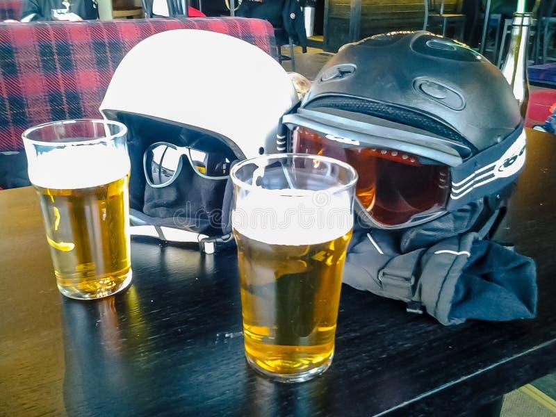 Dois capacetes do esqui que apreciam duas cervejas fotografia de stock royalty free