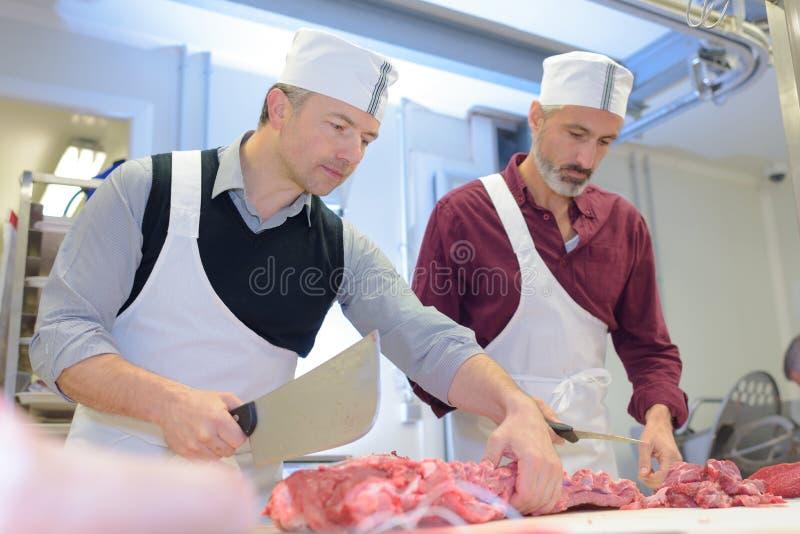 Dois carniceiros que preparam a carne na loja imagens de stock