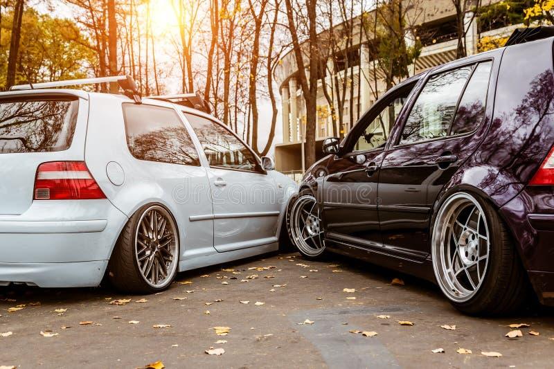 Dois carros azul branco e roxo querem tomar um lugar de estacionamento Problemas de estacionamento na cidade Estacionado firmemen imagens de stock royalty free