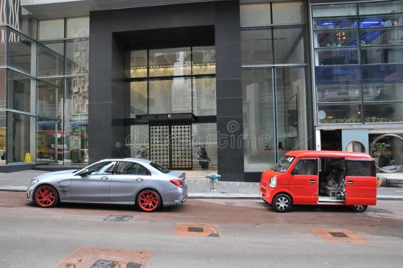 Dois carros muito diferentes em uma rua de Hong Kong na frente das construções modernas foto de stock royalty free