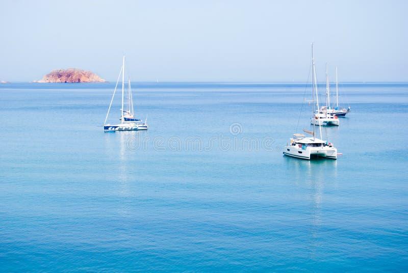 Dois catamarãs e três veleiros ancorados no meio do mar fotografia de stock