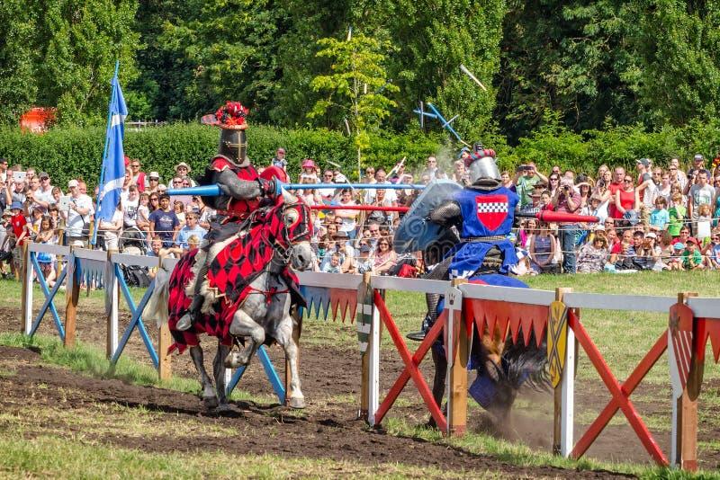 Dois cavaleiro têm o contato pesado das lanças no competiam jousting imagem de stock