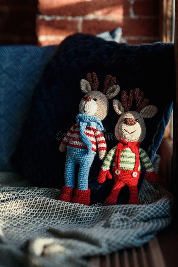 Dois cervos à moda do amigurumi em suportes listrados do laço das camisetas, do lenço e de borboleta na soleira imagens de stock