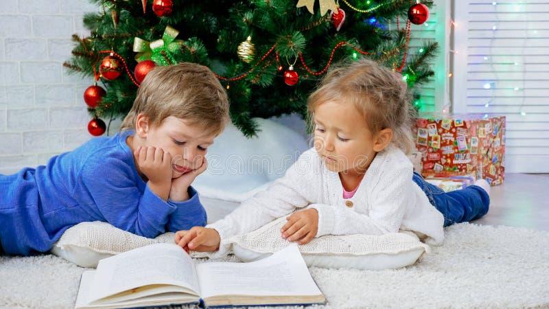 Dois childes bonitos que encontram-se no livro do assoalho e de leitura na Noite de Natal imagens de stock