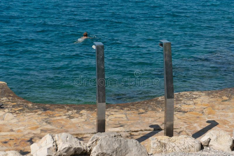 Dois chuveiros do metal na costa da praia do mar de adri?tico as praias Eco-amig?veis identificaram por meio de uma bandeira azul imagem de stock royalty free