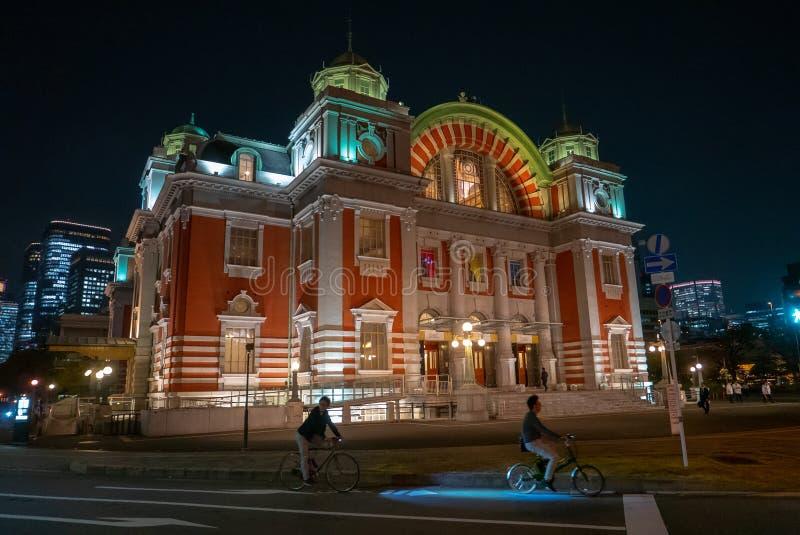 Dois ciclistas passam por Osaka Central Public Hall na noite imagem de stock royalty free