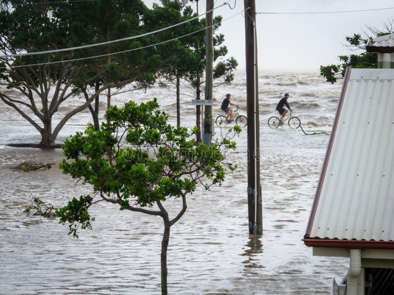 Dois ciclistas pelo mar durante inundações de Brisbane imagens de stock royalty free