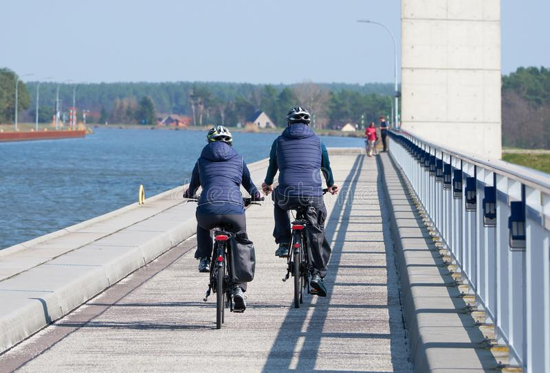 Dois ciclistas que cruzam a ponte da calha em Hohenwarthe foto de stock