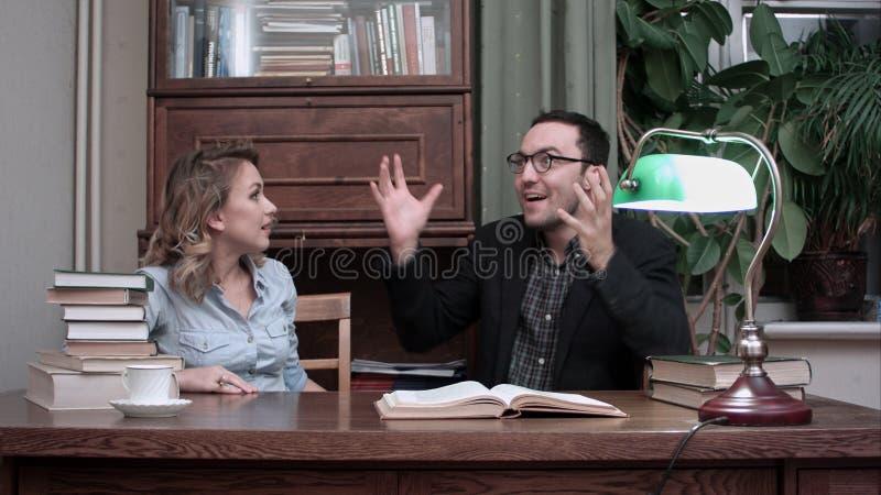 Dois cientistas novos que têm o clique que senta-se na tabela com um livro aberto imagem de stock royalty free