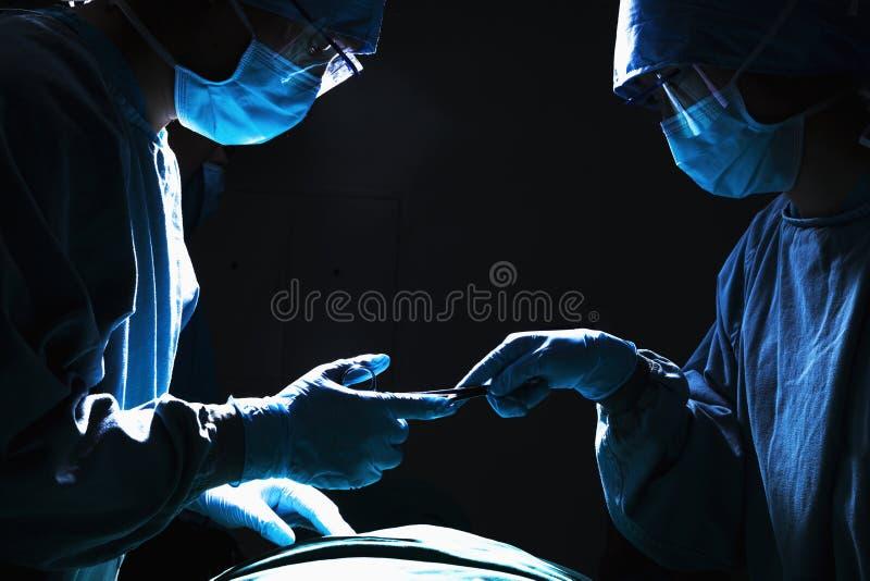 Dois cirurgiões que trabalham e que passam o equipamento cirúrgico na sala de operações, escura fotos de stock