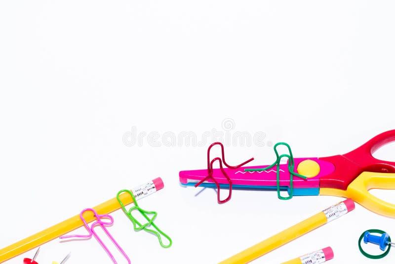 Dois clipes de papel que falam, sentando-se em um ziguezague scissors e dois que encontram-se e que falam no lápis Vida diminuta  fotografia de stock royalty free