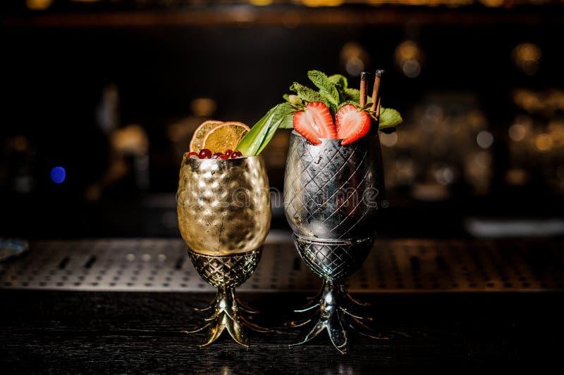 Dois cocktail frescos no abacaxi formam copos com morangos e hortelã e bagas e laranja fotos de stock royalty free
