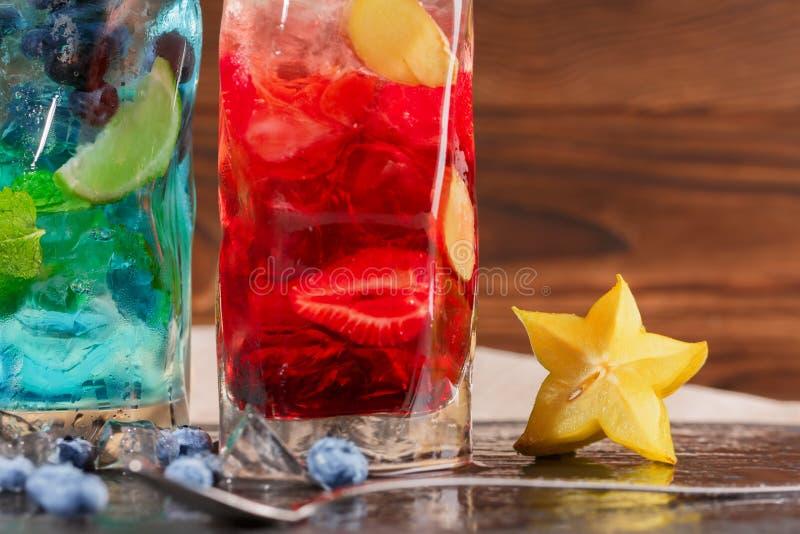 Dois cocktail multi-coloridos frescos com hortelã, cal, carambola, gelo e bagas em um fundo de madeira Bebidas de refrescamento d fotos de stock royalty free