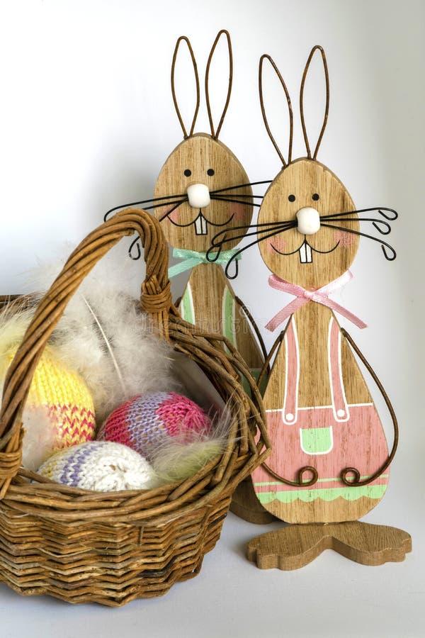 Dois coelhinhos da Páscoa de madeira perto de uma cesta de vime com três fizeram crochê ovos na frente de um fundo brilhante fotos de stock