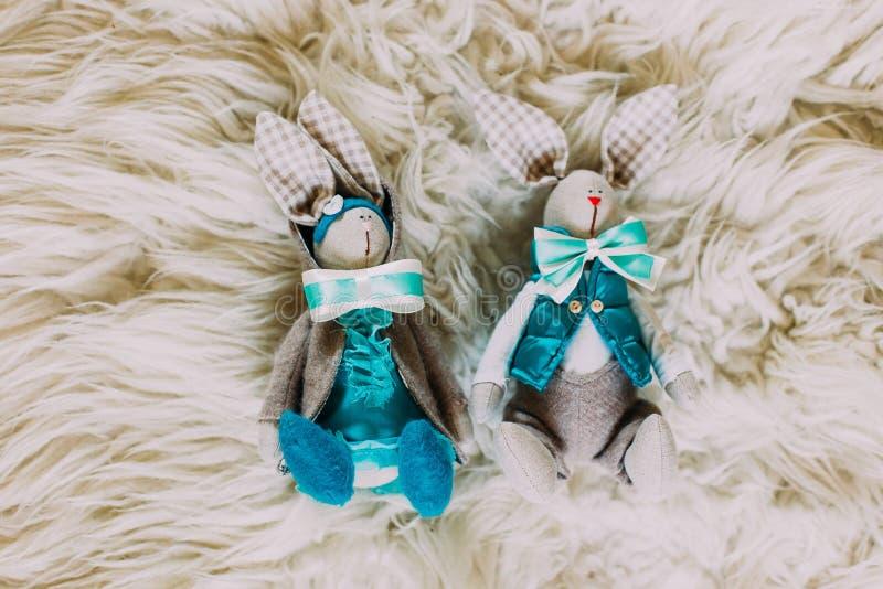 Dois coelhos bonitos do brinquedo nos laços no fundo branco imagens de stock royalty free