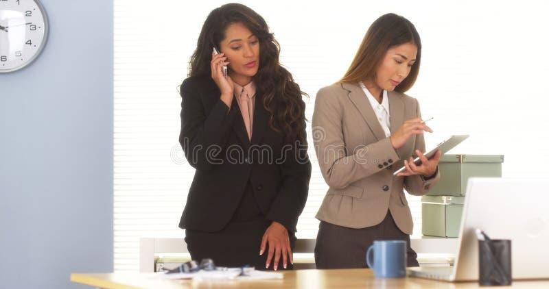 Dois colegas da raça misturada que falam no smartphone e que usam a tabuleta foto de stock royalty free