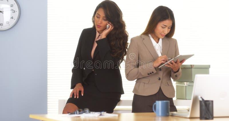 Dois colegas da raça misturada que falam no telefone celular e que usam a tabuleta imagens de stock