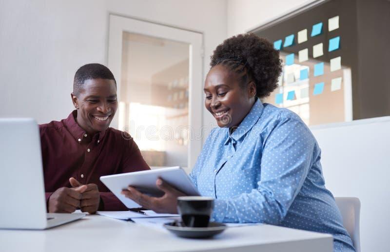 Dois colegas de escritório africanos novos que trabalham com uma tabuleta foto de stock