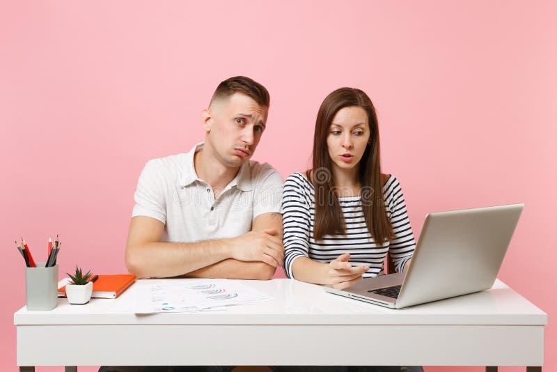Dois colegas de sorriso do homem da mulher de negócio sentam o trabalho na mesa branca com o portátil contemporâneo no fundo cor- fotografia de stock