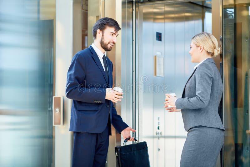 Dois colegas do negócio que encontram-se pelo elevador imagens de stock royalty free