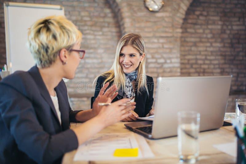 Dois colegas fêmeas novos no escritório, trabalhando junto imagens de stock royalty free