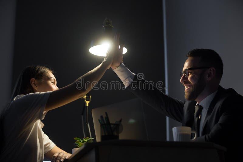 Dois colegas felizes que dão a elevação cinco no escritório na noite foto de stock