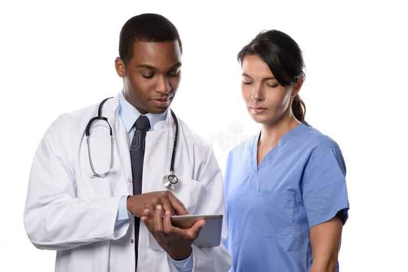Dois colegas médicos que consultam um tabuleta-PC imagens de stock