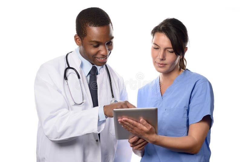 Dois colegas médicos que consultam um tabuleta-PC imagem de stock