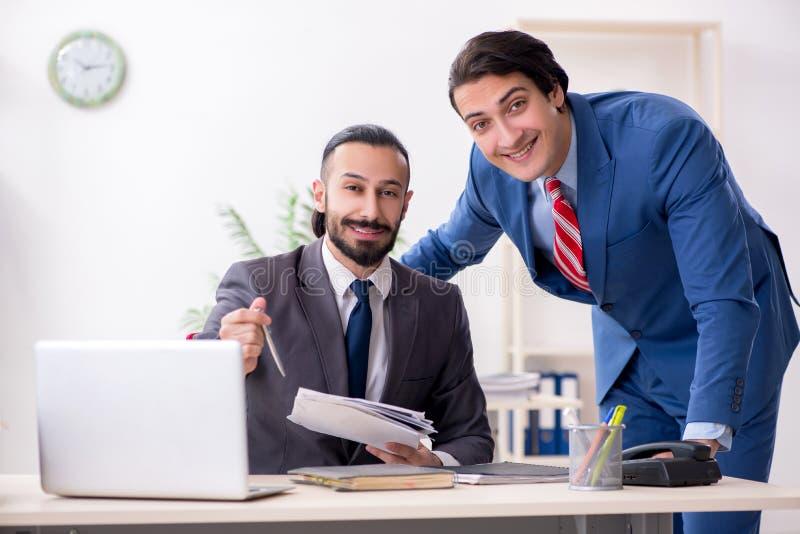 Dois colegas masculinos no escrit?rio imagem de stock royalty free