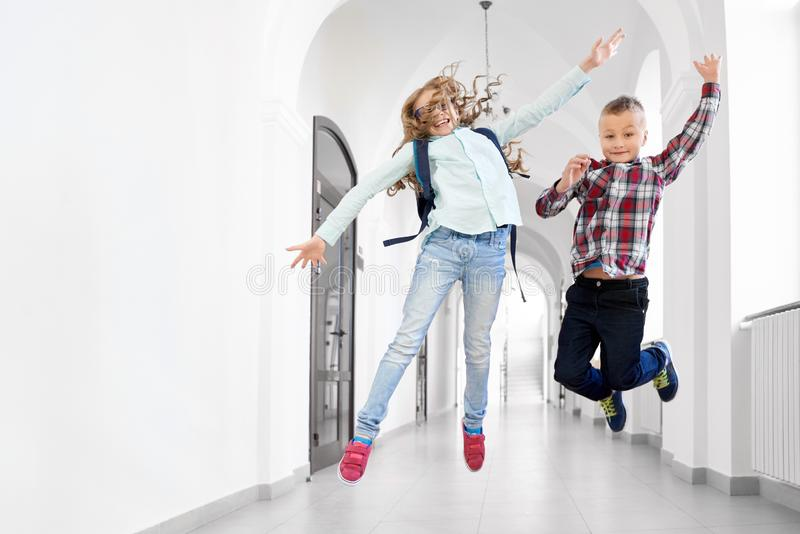 Dois colegas menino e menina dos melhores amigos que saltam acima foto de stock