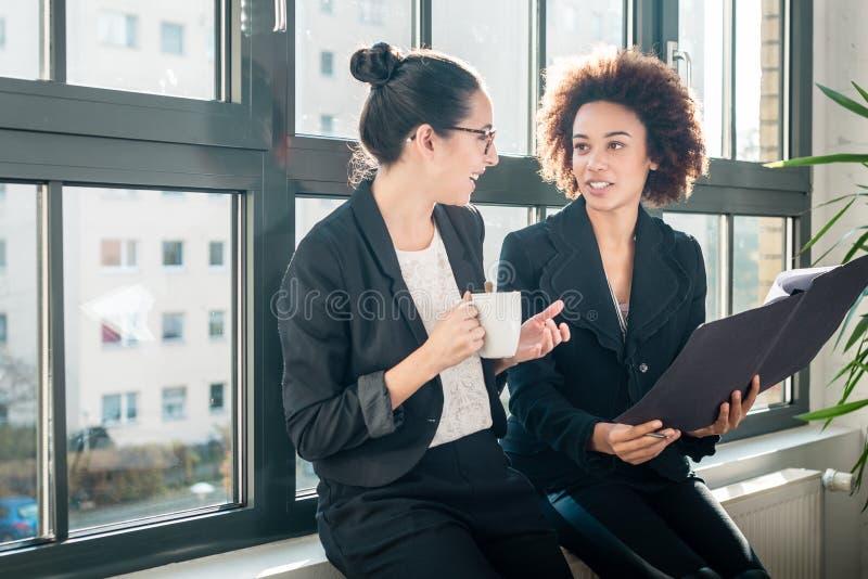 Dois colegas novos que reveem relatórios comerciais durante a ruptura imagem de stock