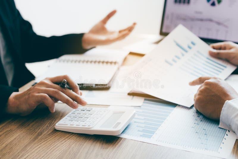 Dois colegas novos que usam a calculadora junto e o gráfico do relatório sumário da análise em um escritório moderno fotos de stock
