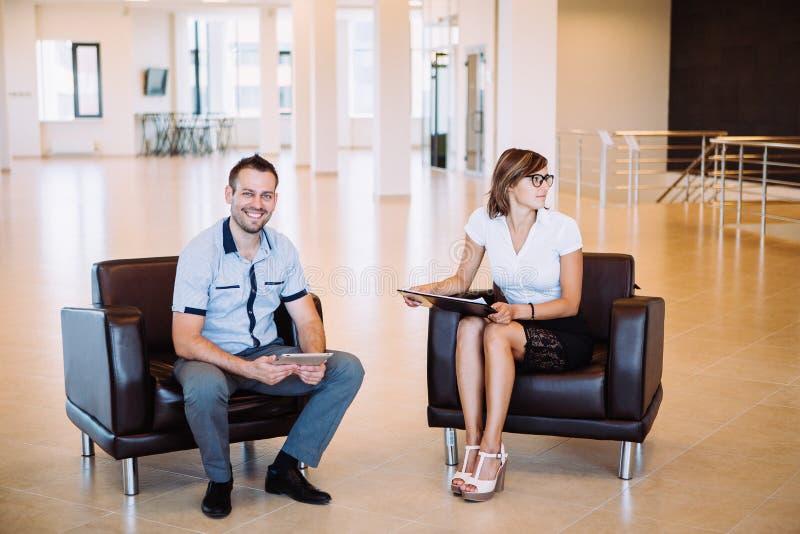 Dois colegas que discutem as ideias do negócio que sentam-se nas cadeiras no escritório foto de stock royalty free